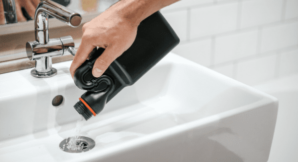 pouring drain cleaner in sink