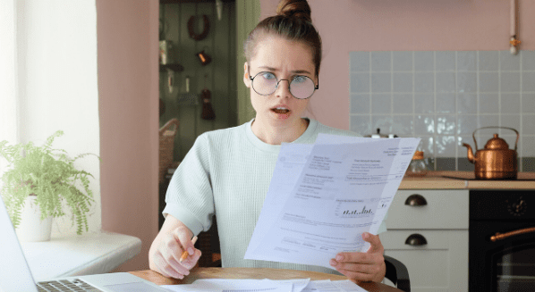 woman shocked looking at utility bill